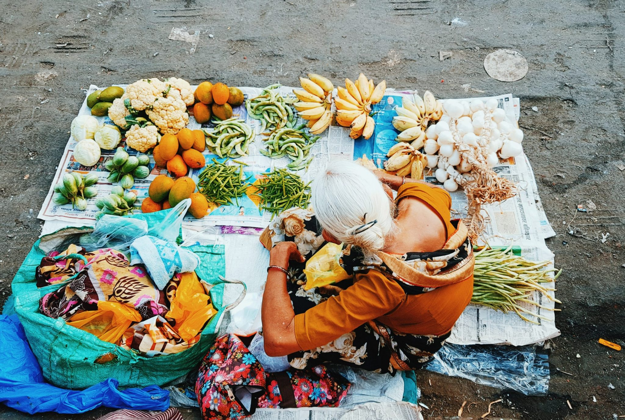 Women sitting on ground surrounded by fruits and vegetables