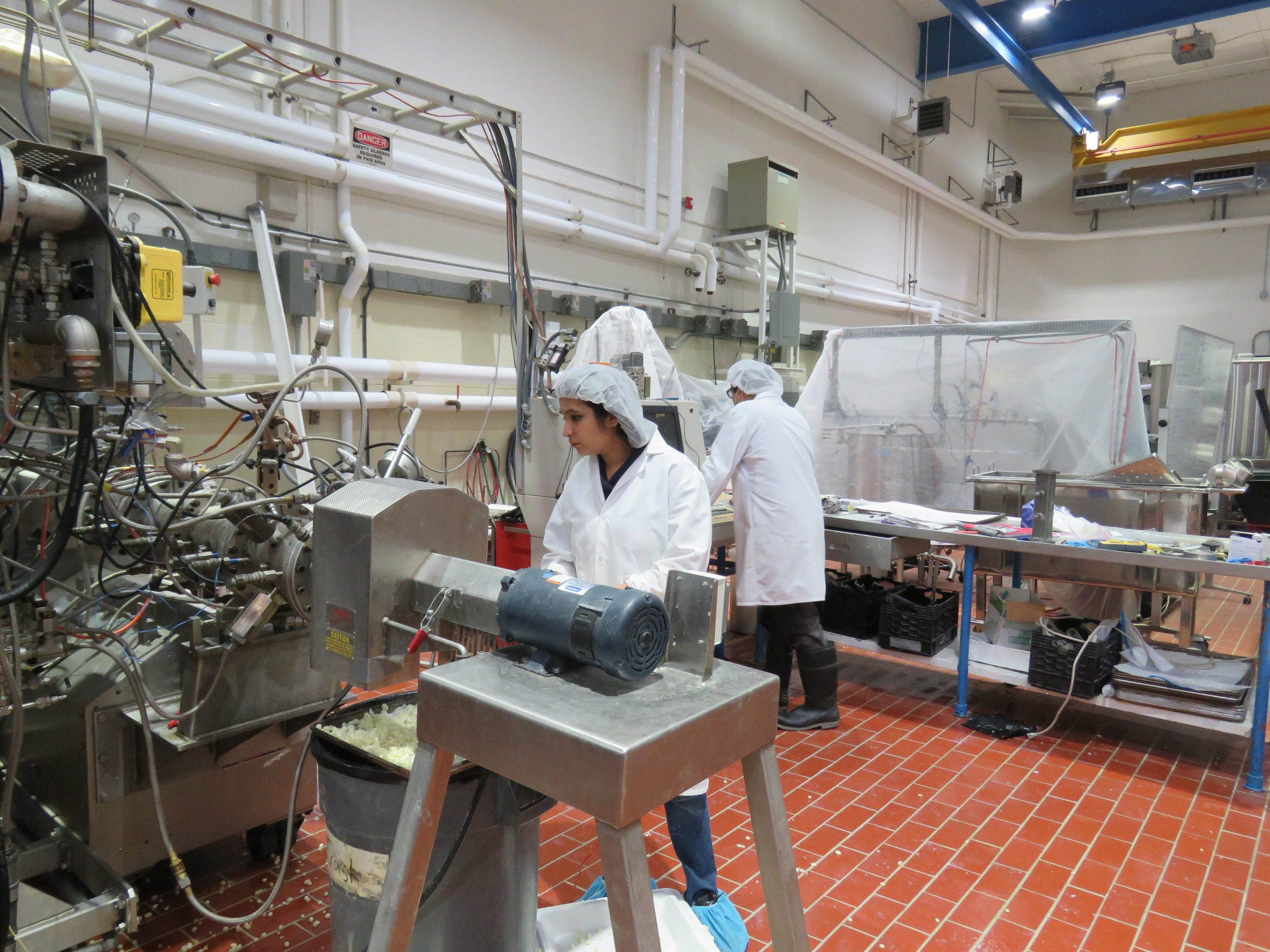 Bindvi Arora stands behind an extruder machine