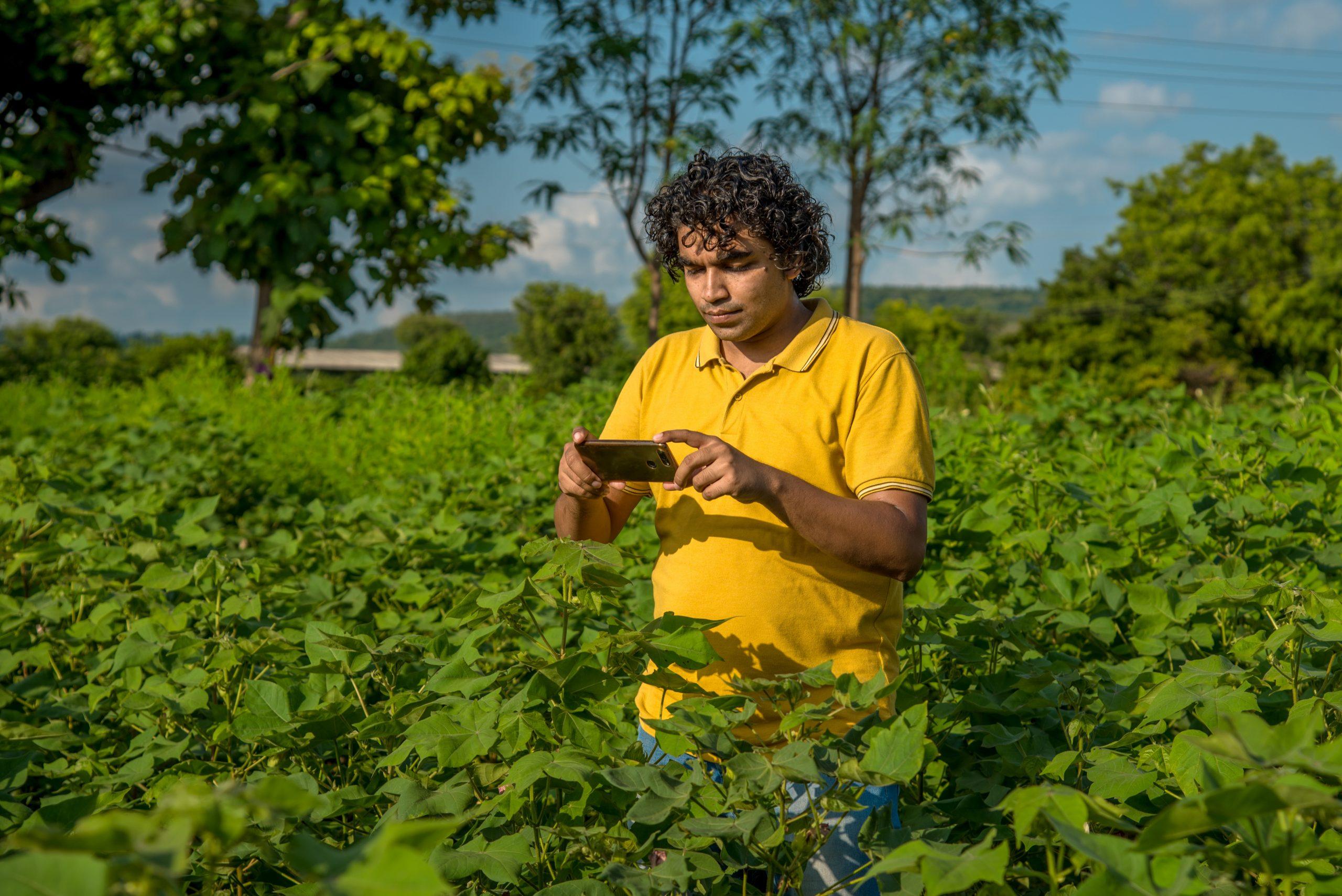 A man holding a phone on a farm