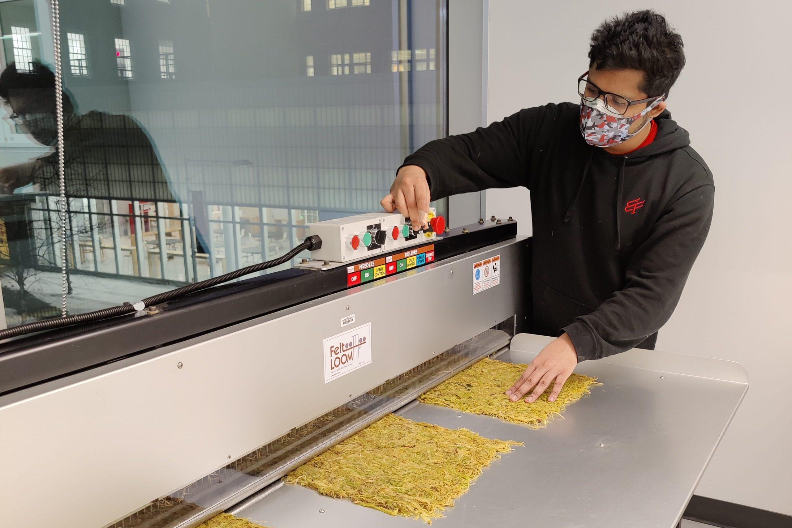 A man operating a machine making mats of straw