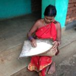 woman picking through a bushel of grains
