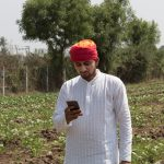 A farmer looking at a mobile phone