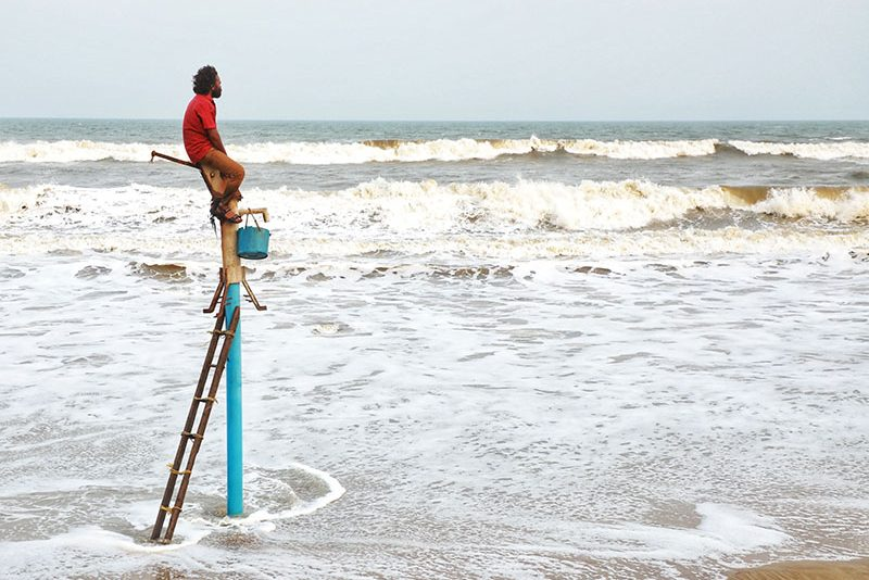 A man on a ladder staring at the sea