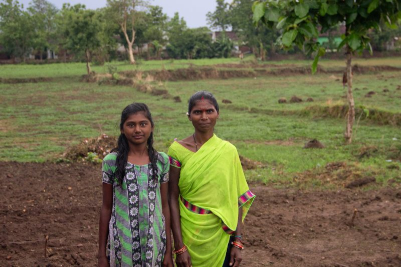 A mother and daughter standing on farmland