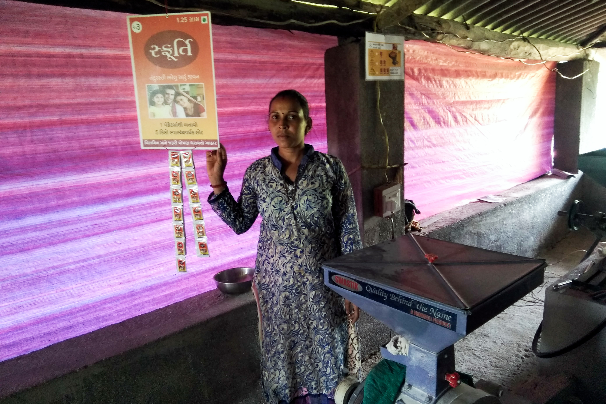 A woman holding a Sfurti sign next to a flour mill