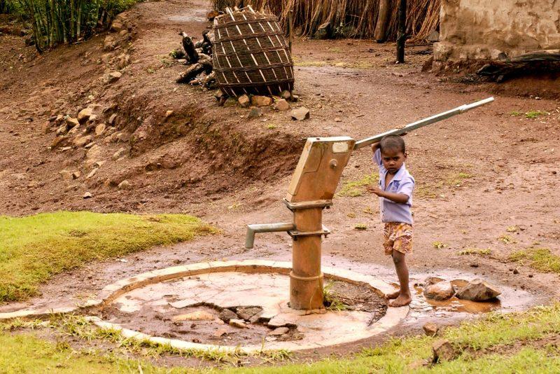 A boy holding onto a water pump