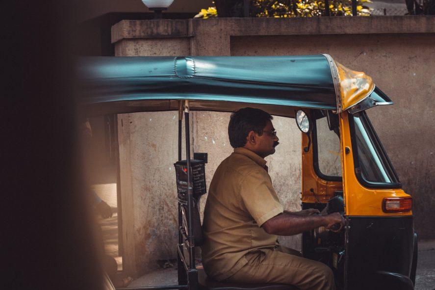 a man sitting in a motorized rickshaw