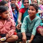 Children sitting and eating sweet potatoes